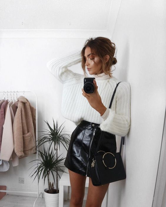 an oversized white jumper, a black leather mini skirt with a zip and a black bag for a sexy look