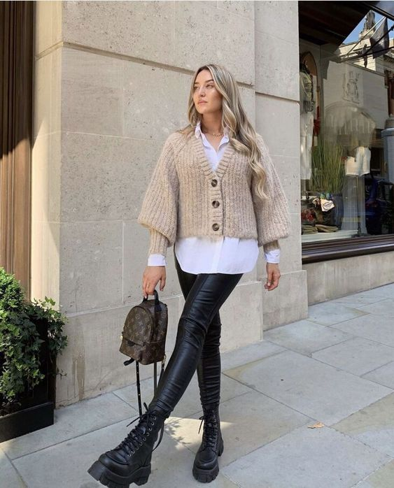 black leather leggings, black boots, a brown backpack and a white shirt plus a tan cardigan over it
