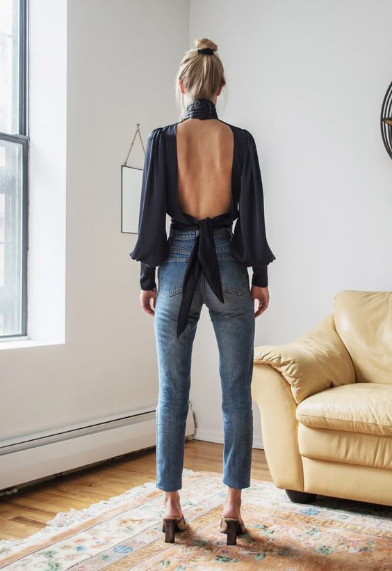 blue cropped jeans, a black high neck blouse with an open tied back and long sleeves plus heels