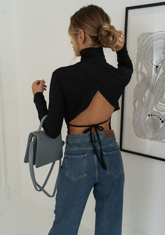 blue high waisted straight jeans, a black draped turtleneck with a tied open back and a grey bag