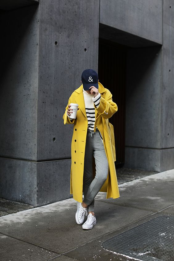 grey joggers, a striped sweater, a lemon yellow midi coat, white sneakers and a cap for winter