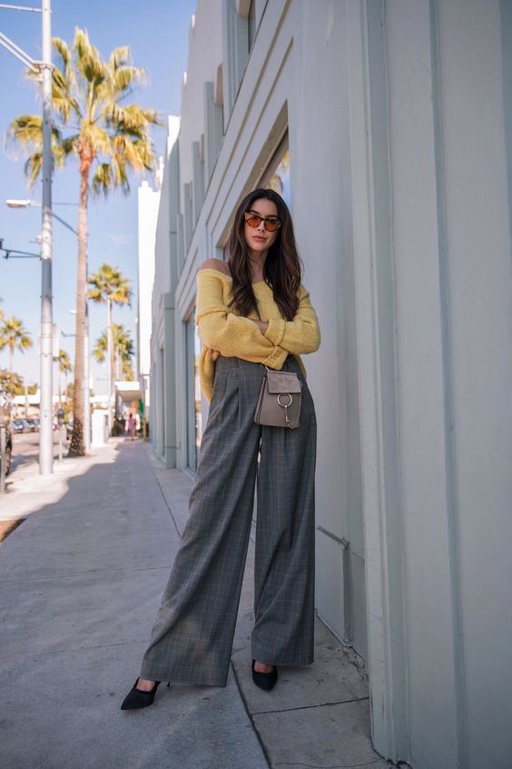 grey plaid wideleg pants, a yellow off the shoulder sweater, black heels and a small grey bag