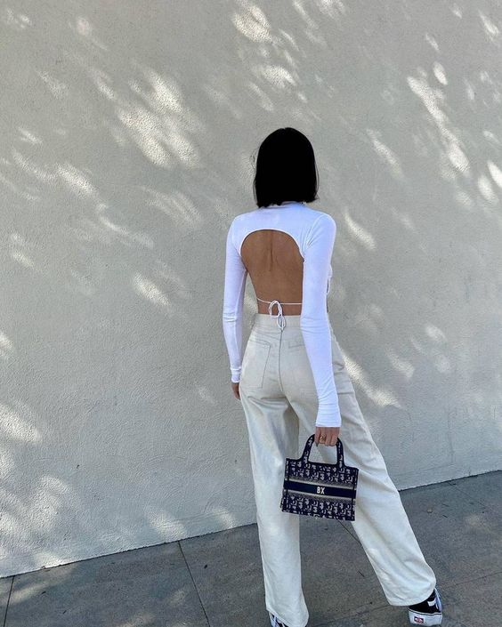 neutral jeans, a white crop top with a tied open back, black sneakers, a black bag