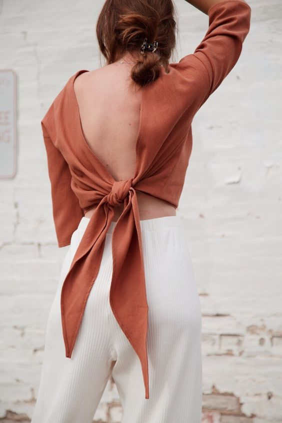 white ribbed high waisted pants, a rust-colored open tied back top with long sleeves for a chic look