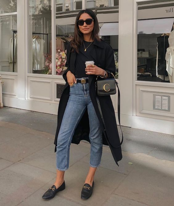 a chic look with a black top, light blue cropped jeans, black loafers, a black trench and a black bag
