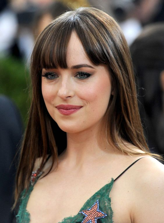 Dakota Johnson wearing long flat hair down plus a fringe and looks very much in trend