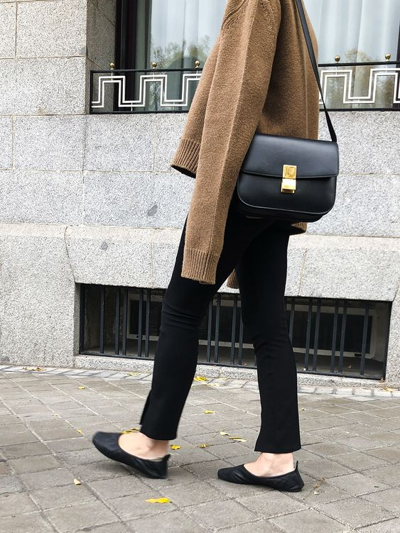 a tan sweater, black pants, black flats and a black bag for a cold spring day