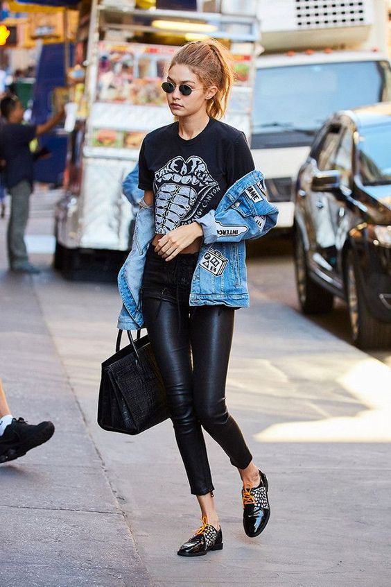 Gigi Hadid wearing a printed t-shirt, black leather pants, a denim jacket, embellished Derby shoes and a tote