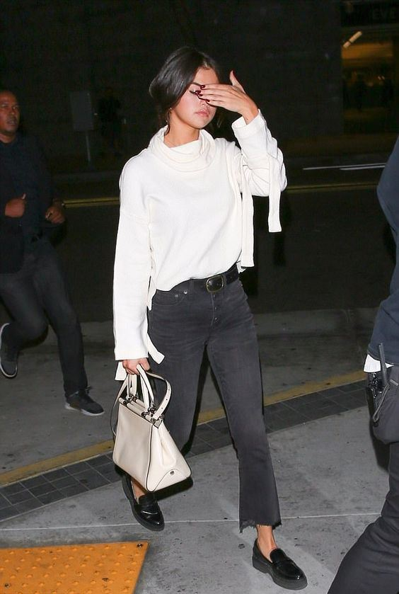 Selena Gomez wearing a white top, a scarf, black jeans, black chunky loafers and a creamy bag
