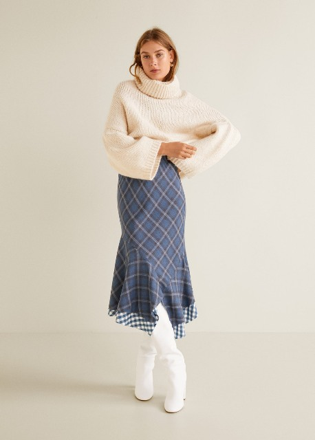 With beige loose turtleneck and white high boots