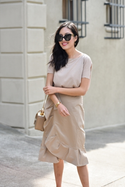 With beige shirt, beige leather bag and sunglasses