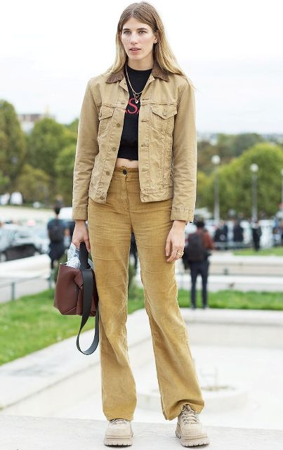 With black crop shirt, beige jacket, brown bag and beige flat boots