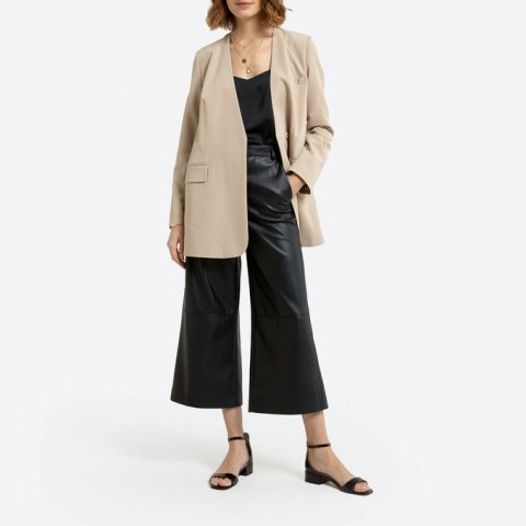 With black shirt, black leather culottes and black ankle strap shoes