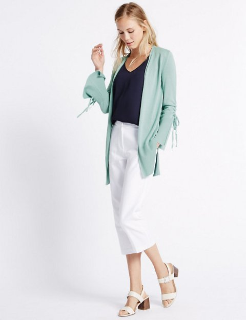 With black shirt, white culottes and white sandals