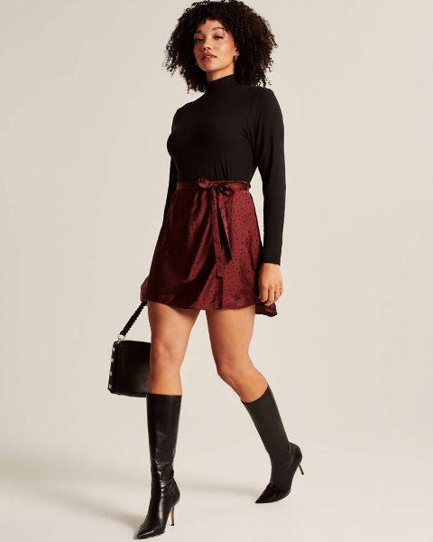 With black turtleneck, black bag and black high boots