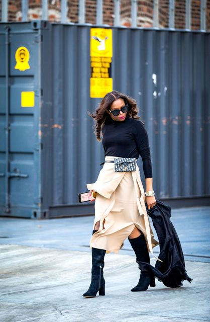 With black turtleneck, black jacket, beige midi skirt and suede high boots