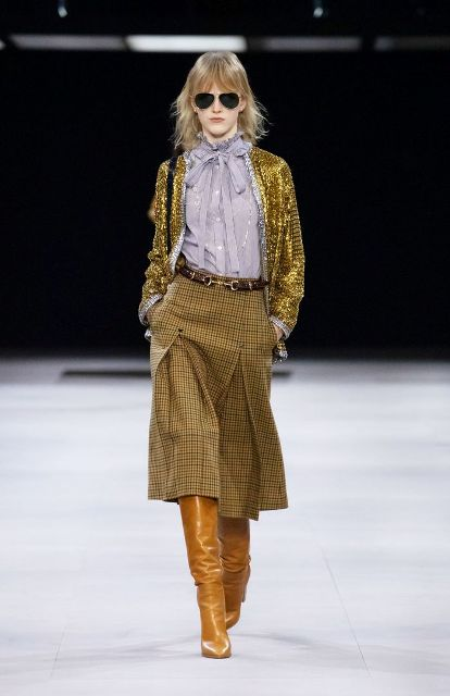 With golden jacket, checked midi skirt, black bag and brown leather high boots