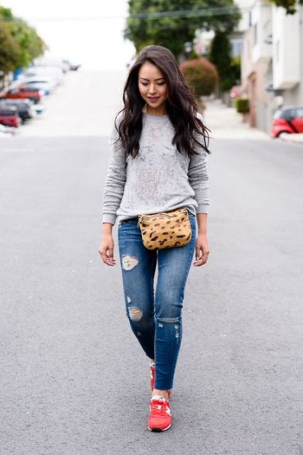 With gray sweatshirt, distressed jeans and red sneakers