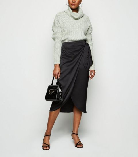 With gray turtleneck sweater, black bag and black sandals