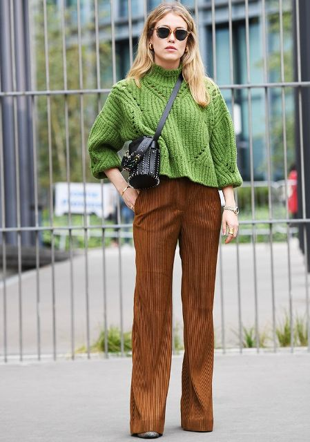 With green loose sweater, black embellished bag and printed boots