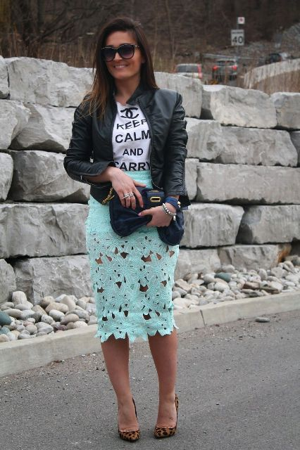 With labeled t-shirt, black leather jacket, black clutch and leopard printed pumps