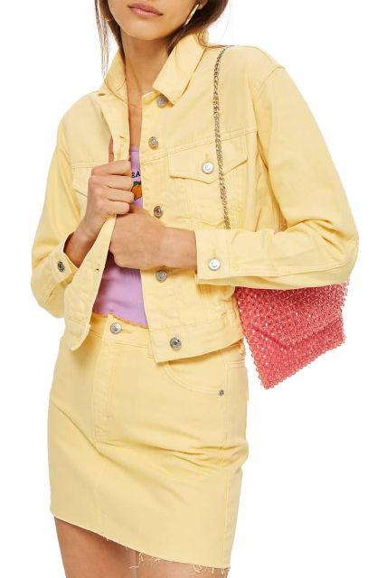 With lilac shirt, light yellow mini skirt and chain strap bag