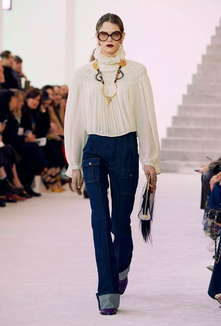 With navy blue flare jeans, necklace, clutch and purple boots
