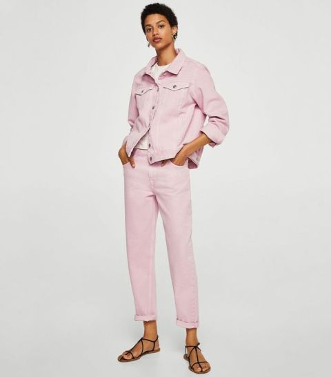 With pale pink cuffed jeans and black flat shoes