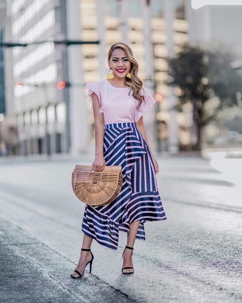 With pale pink ruffle sleeve blouse, straw bag and black high heels