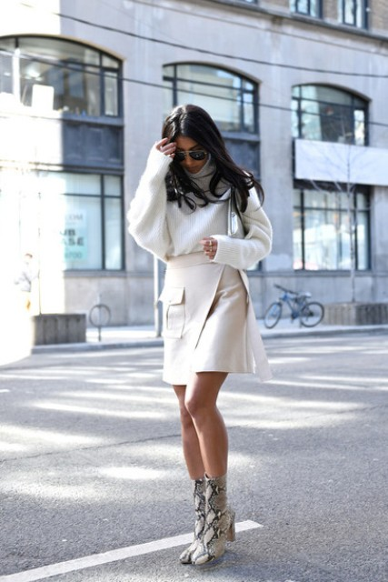 With white loose sweater, clutch and snake printed mid calf boots