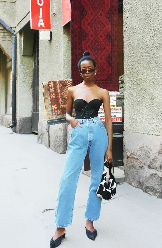 a black corset and blue high waisted jeans, black mules and a printed baguette bag to impress