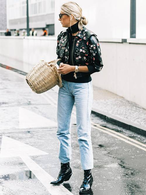 a black floral jacket, a black top, straight leg jeans, black boots and a basket as a bag
