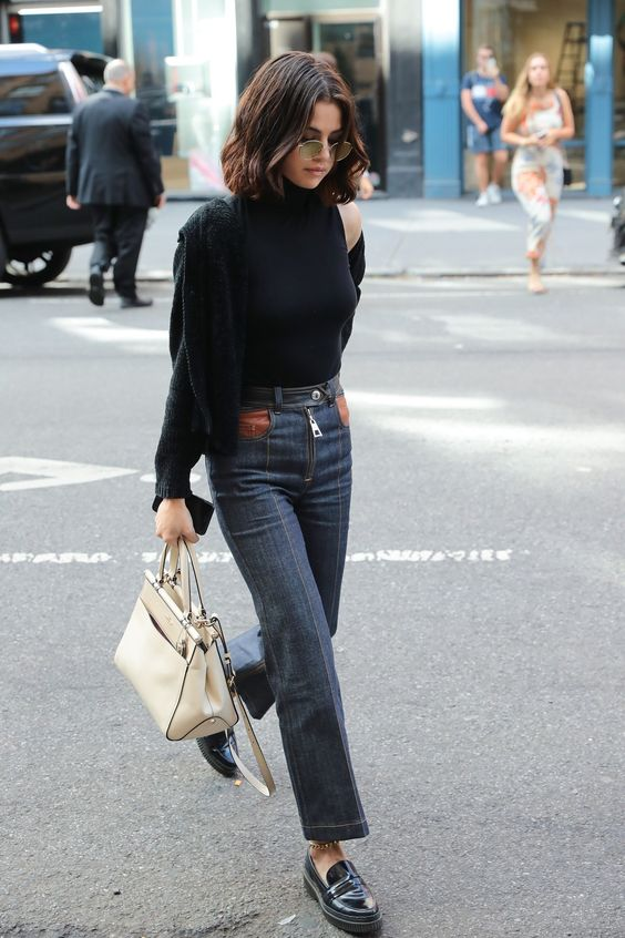a black halter neckline top, a black cardigan, navy jeans, black chunky loafers and a creamy bag