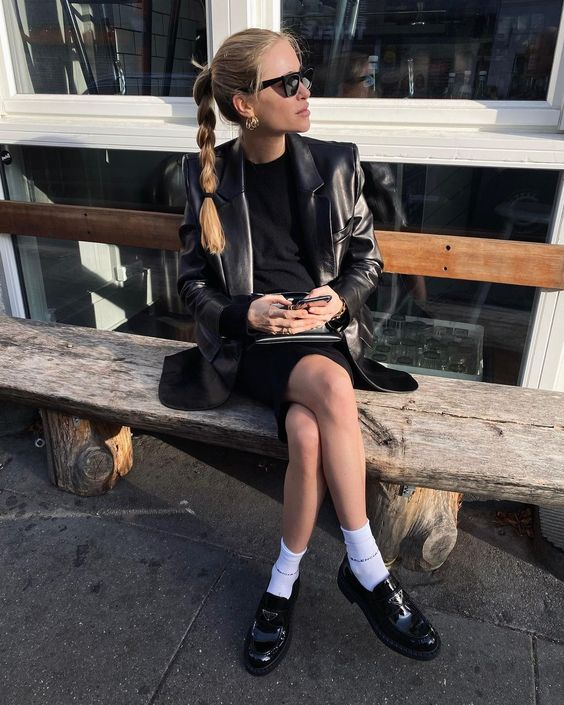 a black mini dress, a black leather jacket, white socks and black chunky loafers for a statement look