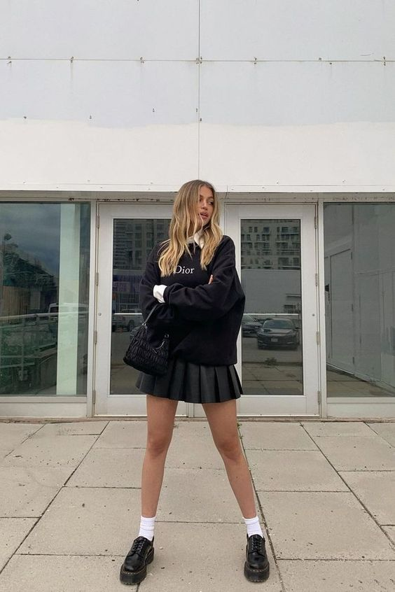 a black pleat mini, a white shirt, a black sweatshirt, white socks, black chunky loafers and a black bag