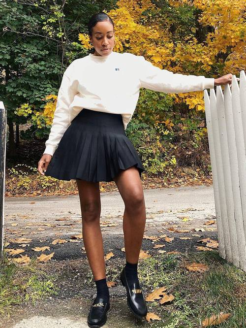 a black pleat mini, a white sweatshirt, black socks and chunky loafers for a trendy look
