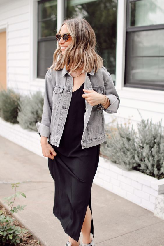 a black slip dress, a neutral denim jacket, a statement necklace and trainers for a relaxed and sexy look