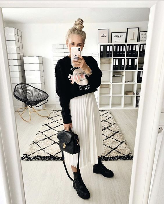 a black sweatshirt, a white pleated midi, comba boots, a black bag and a top knot