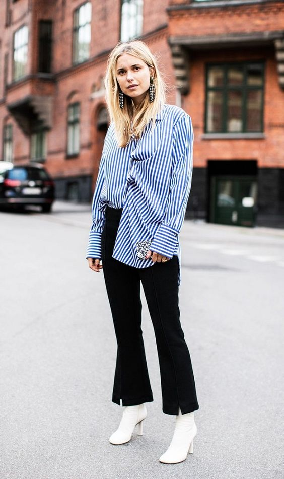 a blue and white oversized shirt, black flare jeans, white ankle boots, statement earrings