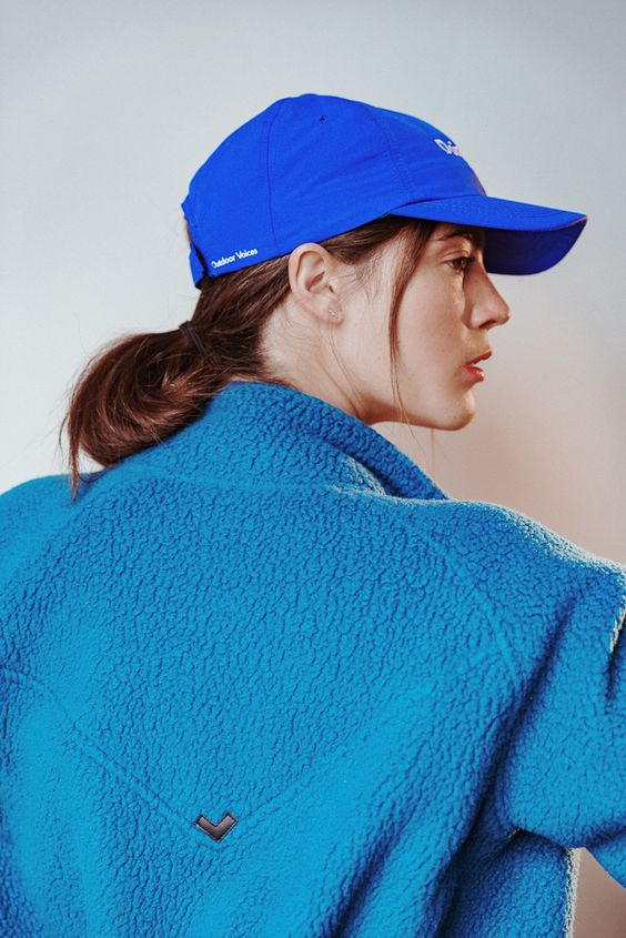 a blue baseball hat paired with a low bun and some locks down for a very relaxed everyday look
