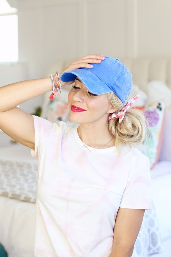 a blue denim baseball cap plus a low messy side bun with a bow for a playful and fun touch