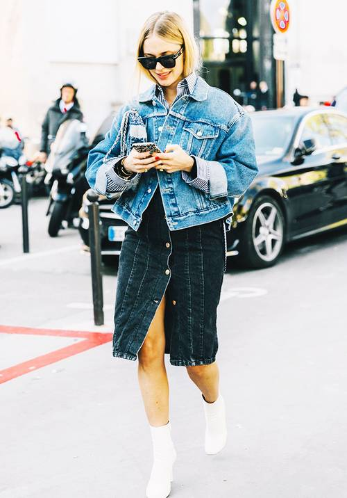a blue denim jacket, a black denim midi with buttons, a clutch and white ankle boots