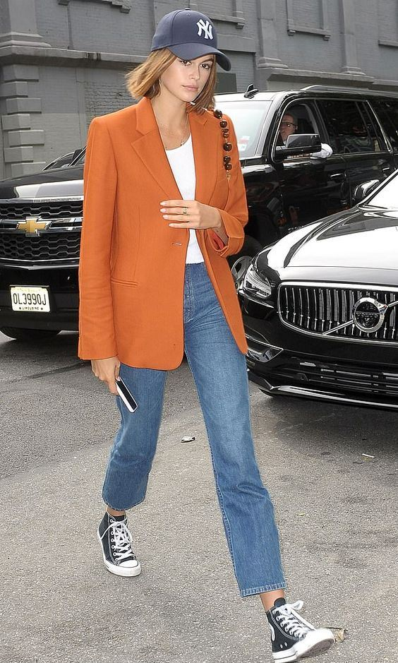 a bright look with a white top, blue jeans, black sneakers, an orange oversized blazer and a navy baseball hat