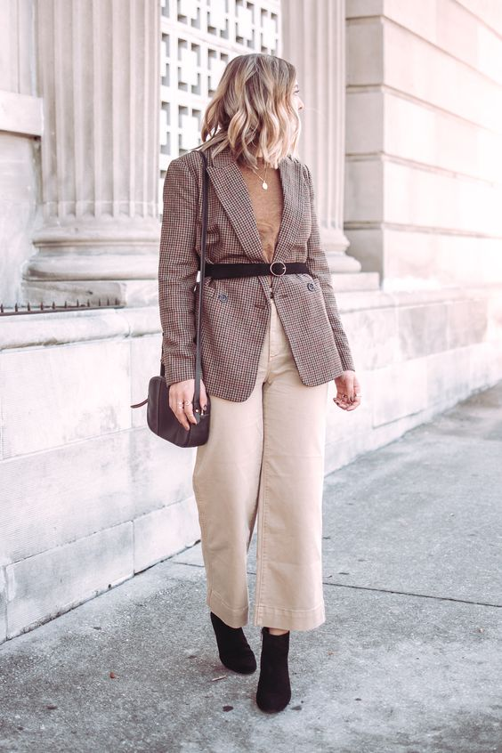 a camel t-shirt, a plaid blazer with a belt, white jeans, black booties and a black bag