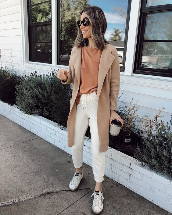 a casual look with a rust-colored tee, creamy joggers, white sneakers, a tan trench