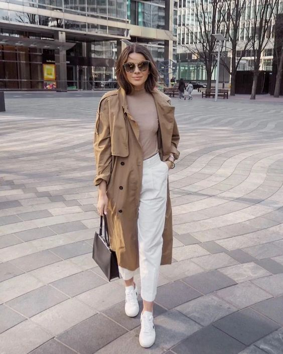 a casual look with a tan top, white high waisted pants, white sneakers, a camel trench and a black bag