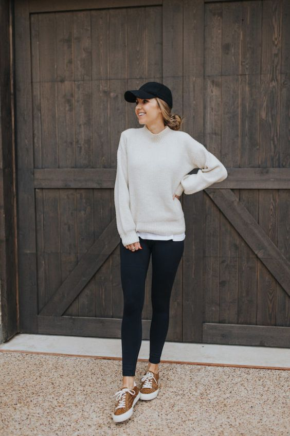 a casual look with black leggings, a white t-shirt, a neutral sweatshirt, brown sneakers and a black baseball hat