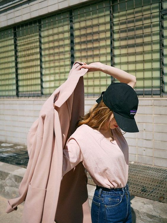 a casual spring outfit with a pink long sleeve top, blue jeans, a pink trench and a black baseball hat