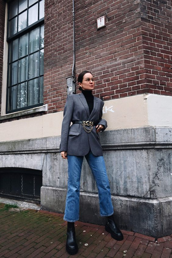 a casual yet very chic look with a black turtleneck, a grey blazer, blue jeans, black boots and a cool black blazer with chains