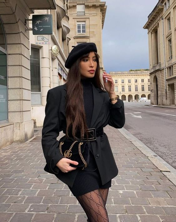 a chic all-black outfit with a sweater dress, a blazer, a belt, a beret, printed tights and a black bag